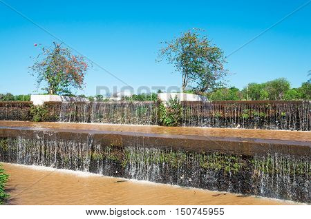 Falling cascading water of a lake in a park. Vegetation around with plants and some flowers. Beautiful sunny day with blue sky background. Natural wonders of South America.