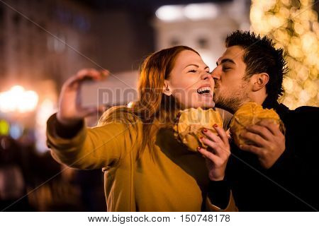 Young couple taking mobile phone selfie with sandwiches in their hands - outdoor at christmas market
