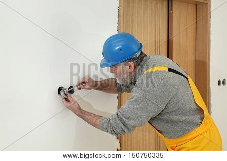 Electrician installing electrical plug at wall and using voltage testing screwdriver