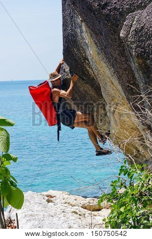 a strong and happy man climbing on high rock over the sea with a hut and a red seabag.