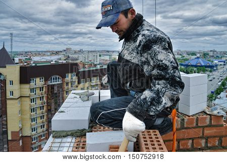 Tyumen, Russia - May 23, 2008: Construction of 18 floor brick residental house at intersection of streets of Gercena and Chelyuskincev. Bricklayer behind works on 18th floor