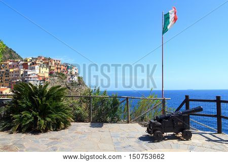 Old cannon Italian flag and Cinque Terre village Manarola with colorful houses and Mediterranean Sea Italy