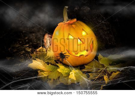 Grinning pumpkin lantern or jack-o'-lantern is one of the symbols of Halloween. Halloween attribute. In the forest near the stone