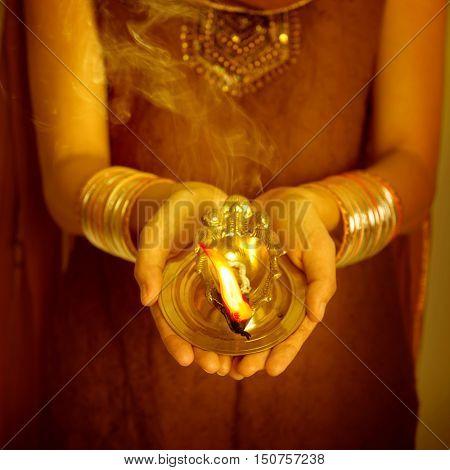 Close up Indian woman in traditional sari hands holding diya and celebrating Diwali or deepavali, fesitval of lights.