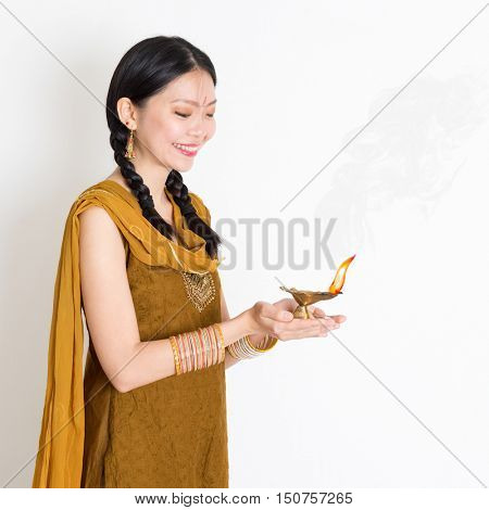 Young mixed race Indian Chinese female in traditional dress hands holding diya oil lamp and celebrating Diwali or deepavali, fesitval of lights.