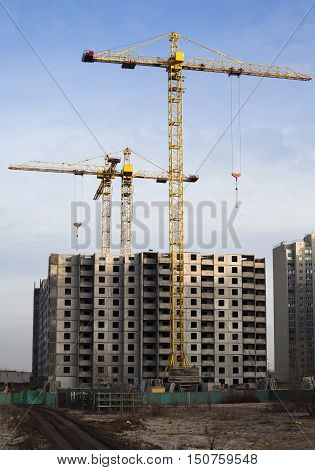 Tower cranes and high-rise building in the construction site.