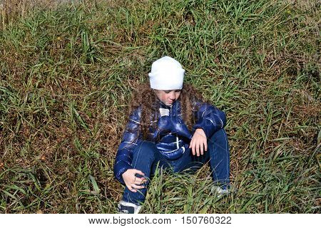 A girl with curly hair sits on a faded grass and looking down