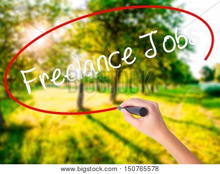 Woman Hand Writing Freelance Jobs With A Marker Over Transparent Board
