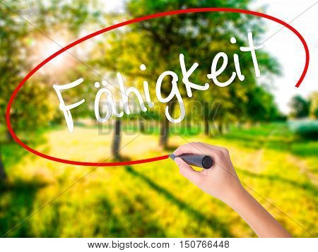 Woman Hand Writing Fahigkeit (ability In German) With A Marker Over Transparent Board