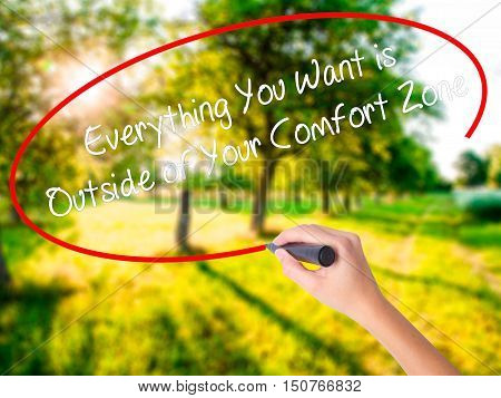 Woman Hand Writing Everything You Want Is Outside Of Your Comfort Zone With A Marker Over Transparen