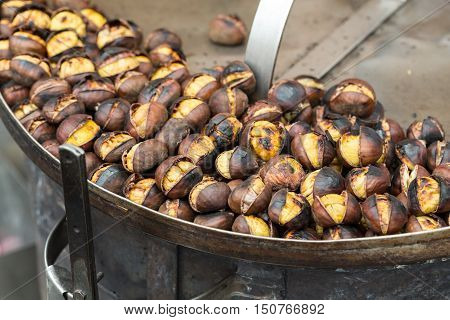 Roasting chestnuts on the grill by a street vendor in Rome Italy