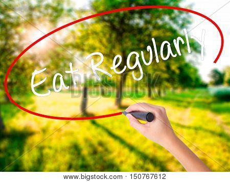 Woman Hand Writing Eat Regularly With A Marker Over Transparent Board .
