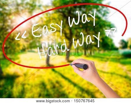 Woman Hand Writing Easy Way - Hard Way With A Marker Over Transparent Board .