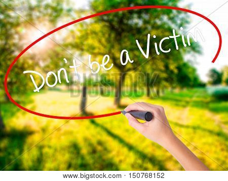 Woman Hand Writing Don't Be A Victim  With A Marker Over Transparent Board