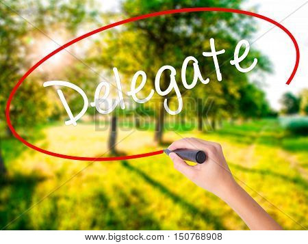 Woman Hand Writing Delegate With A Marker Over Transparent Board