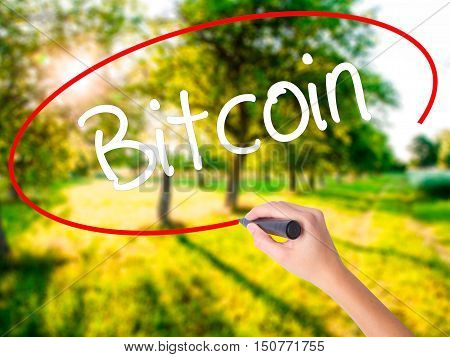 Woman Hand Writing Bitcoin With A Marker Over Transparent Board .