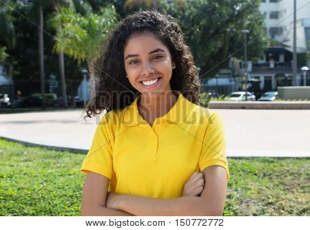 Beautiful latin american girl with long dark hair and crossed arms outdoors in the summer in the city