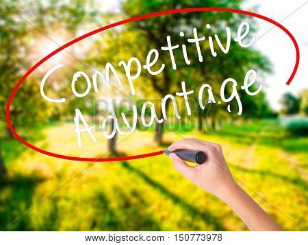 Woman Hand Writing Competitive Advantage With A Marker Over Transparent Board