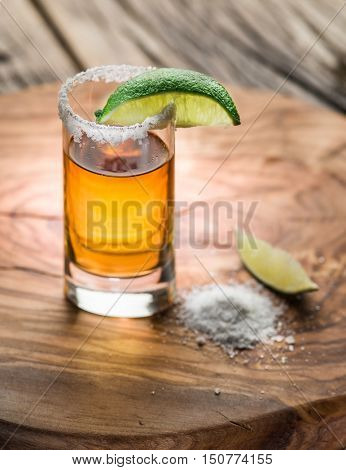 Single shot of tequila served with lime and salt on the wooden background.
