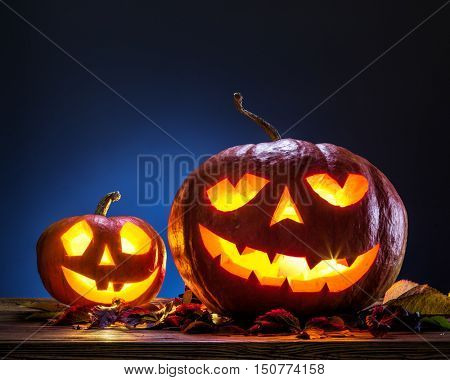 Grinning pumpkin lantern or jack-o'-lantern is one of the symbols of Halloween. Halloween attribute. Wooden background.