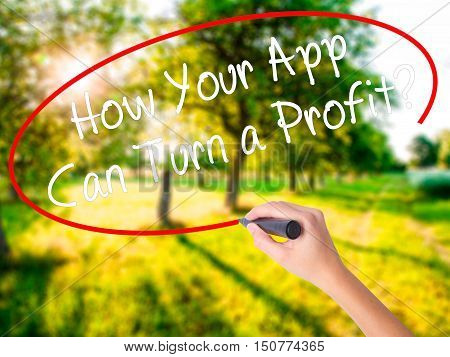 Woman Hand Writing How Your App Can Turn A Profit? With A Marker Over Transparent Board