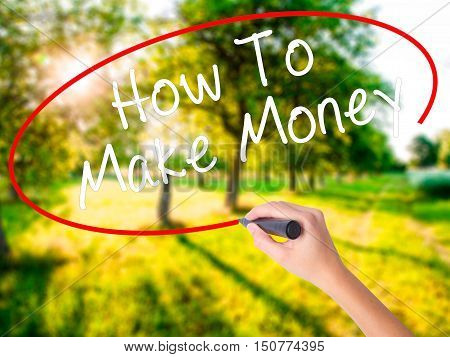 Woman Hand Writing How To Make Money With A Marker Over Transparent Board