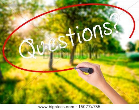 Woman Hand Writing Questions? With A Marker Over Transparent Board