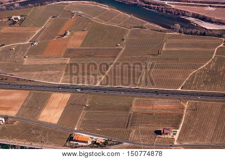 Aerial view with a detail of the Adige Valley in winter with the highway cultivated fields and Adige River in Italy