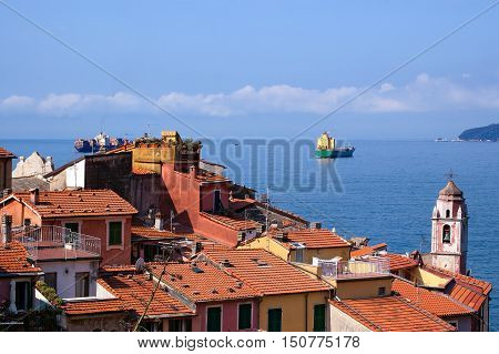 Container ships in the Gulf of La Spezia and cityscape of Tellaro ancient small village in Liguria Lerici La Spezia Italy