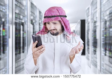Middle eastern businessman reading message on his smartphone and looks disappointed shot in the server room