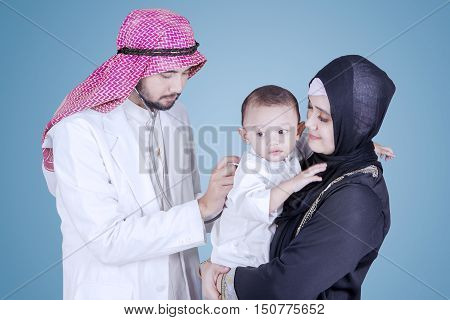 Arabian doctor wearing islamic clothes and using a stethoscope to examine a baby boy
