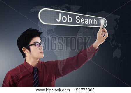 Young Asian businessman pressing a job search button on the virtual screen. Concept of Job Search