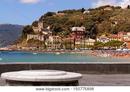 The village of San Terenzo (St. Terenzo) with the beach crowded with sunbathers. Lerici in the Gulf of La Spezia Liguria Italy
