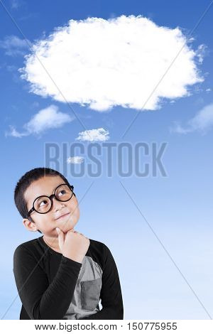 Cute little boy wearing glasses and thinking while looking at a thought bubble