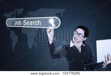 Photo of a young businesswoman touching a job search button on the virtual screen and holding a laptop