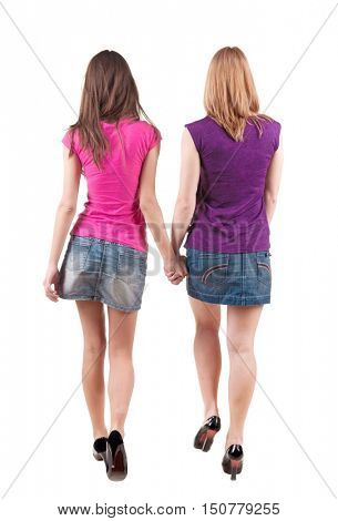 Back view going of two young girl brunette and blonde . Rear view people collection. backside view of person. beautiful woman friends walking. Rear view. Isolated over white background.
