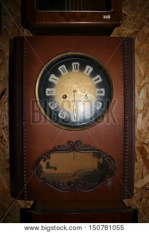 old wall clock brown color with large arrows and pendulum