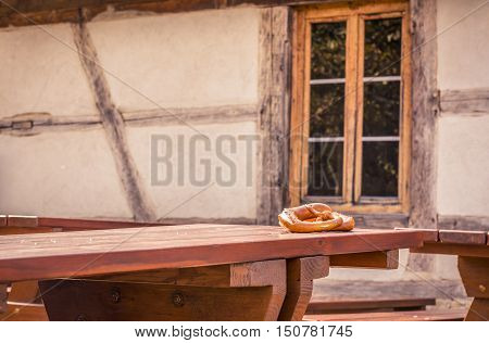 Pretzels on rustic table and German house background - Traditional German pastry treat two pretzels on a wooden table with a medieval architecture house in the background.