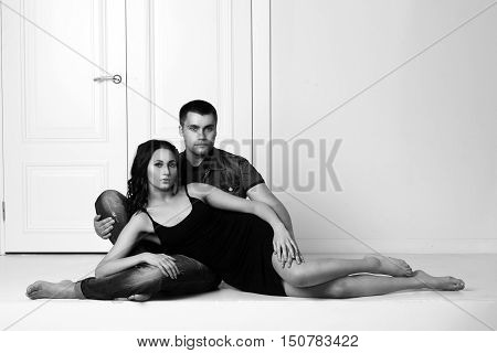 Romantic couple sitting on white floor in brigh white interior and looking at you. Sexy girl in black dress and handsome man