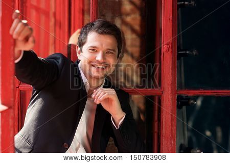 Young happy smiling man sitting near old grunge window with wooden frame in loft interior. Handsome adult model wearing white jacket and black stylish suit