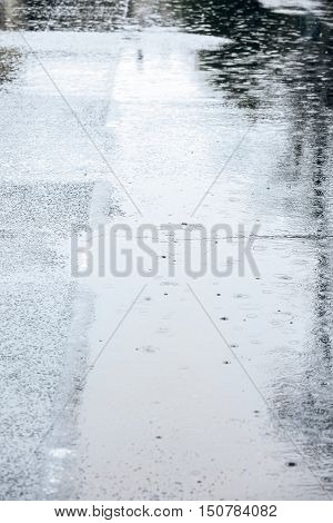 Water Puddles With Falling Raindrops On Asphalt Pavement During Bad Weather