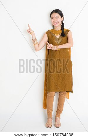 Portrait of young mixed race Indian Chinese female in traditional punjabi dress fingers pointing at copy space, full length standing on plain white background.