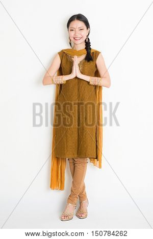 Portrait of mixed race Indian Chinese woman in traditional punjabi dress greeting, full length standing on plain white background.