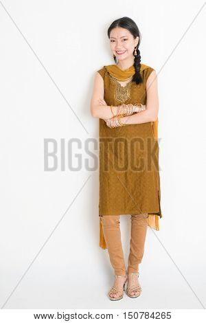 Portrait of young mixed race Indian Chinese female in traditional punjabi dress smiling, full length standing on plain white background.