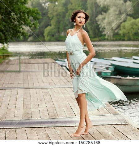 Pretty beautiful girl in light blue dress walking at wooden pier on a summer day