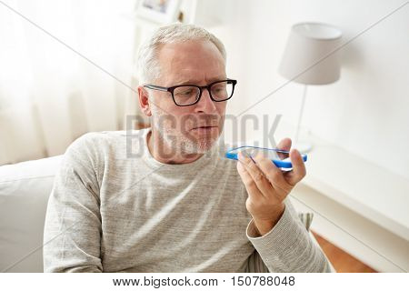 technology, people, lifestyle and communication concept - close up of senior man using voice command recorder or calling on smartphone at home