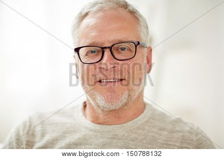 old age, vision and people concept - close up of smiling senior man in glasses