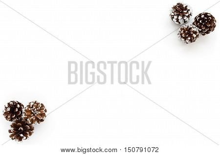 White Christmas Background with six hand painted snowy white pine cones isolated on white background. Three pine cones each in right top corner and left bottom corner.