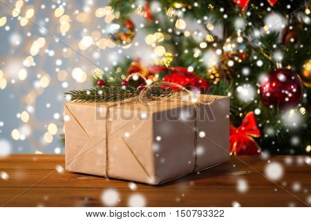 christmas, holidays, presents, new year and decor concept - close up of gift box wrapped into brown mail paper and decorated with fir brunch and rope bow over lights background