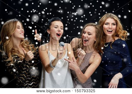 new year party, christmas, winter holidays and people concept - happy women with microphone singing karaoke over black background with snow
